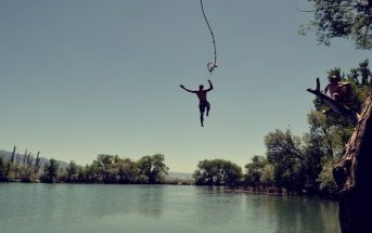 man jumping from rope into lake - concept of taking risks