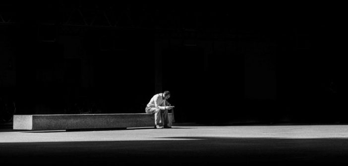 man sitting on concrete bench against black background indicating a simplification of his life
