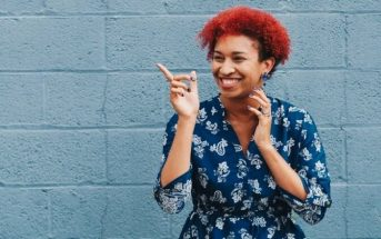 woman smiling and pointing to indicate humor