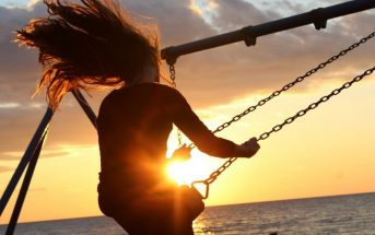 silhouette of woman on swing with sunset in background