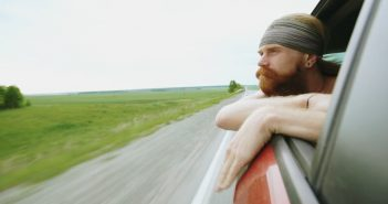 young man with beard looking out car window