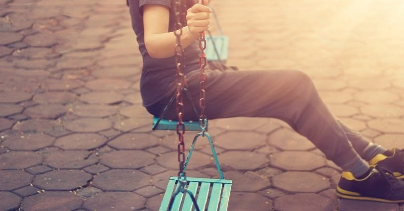 lonely woman on playground swing who has driven her friends away
