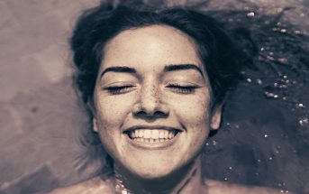 young woman lying in water smiling