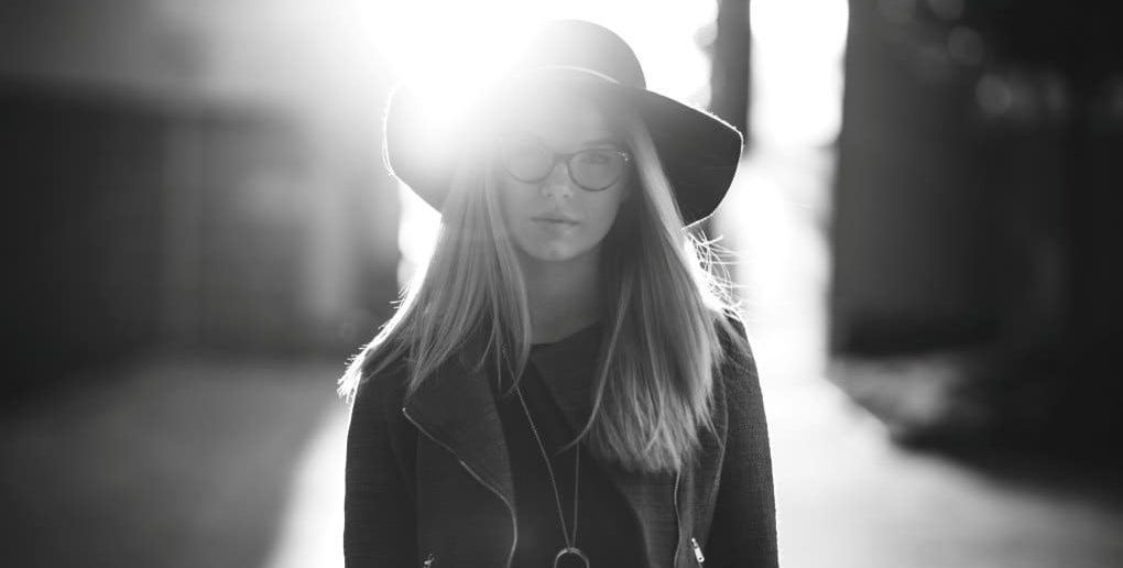 black and white photo of woman in hat on sunny street