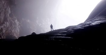 silhouette of person in dark cave walking toward the light
