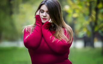 curvy young empath woman in red sweater holding head