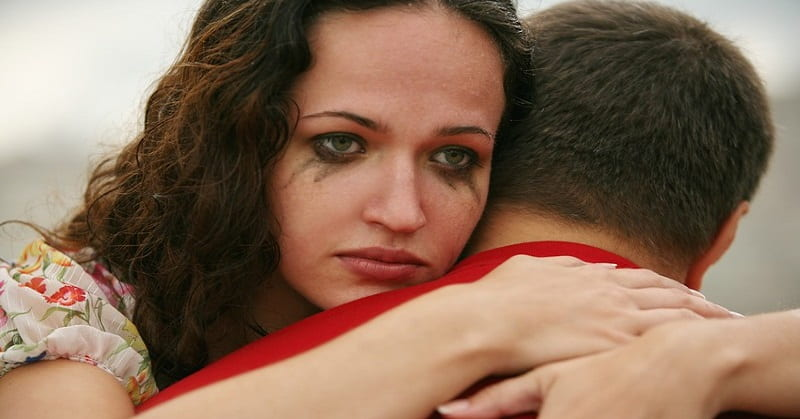 woman with mascara that's run hugging man - showing a breakup