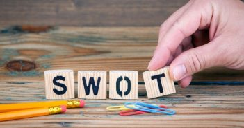 hand making the word SWOT out of tiles