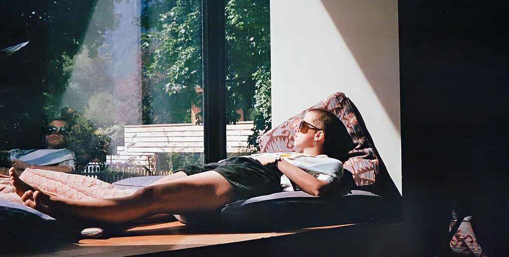 woman relaxing on window ledge in sun