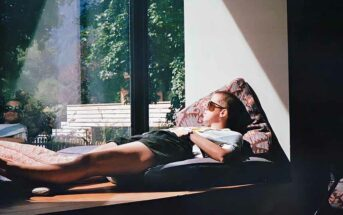 woman relaxing on window ledge in sun