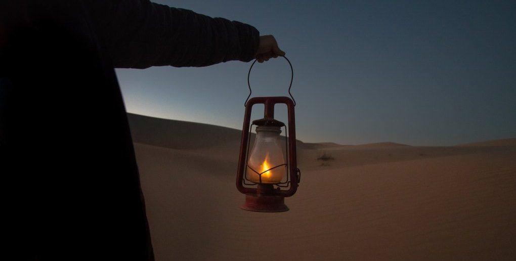 man holding lantern in desert