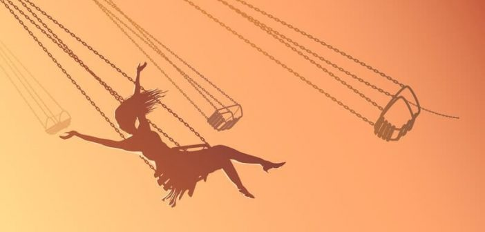 silhouette of young woman on swing against orange sky, showing her inner child
