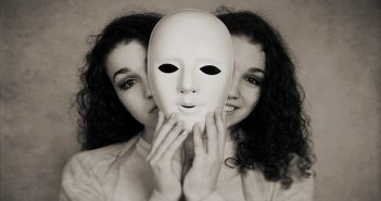 young woman with happy and sad face behind mask - showing mood swings
