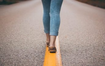 legs and feet of woman walking down middle of road