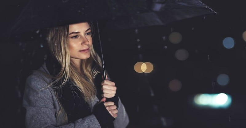 young woman carrying umbrella in the rain
