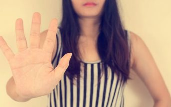 young woman with outstretched palm signalling her saying no to someone