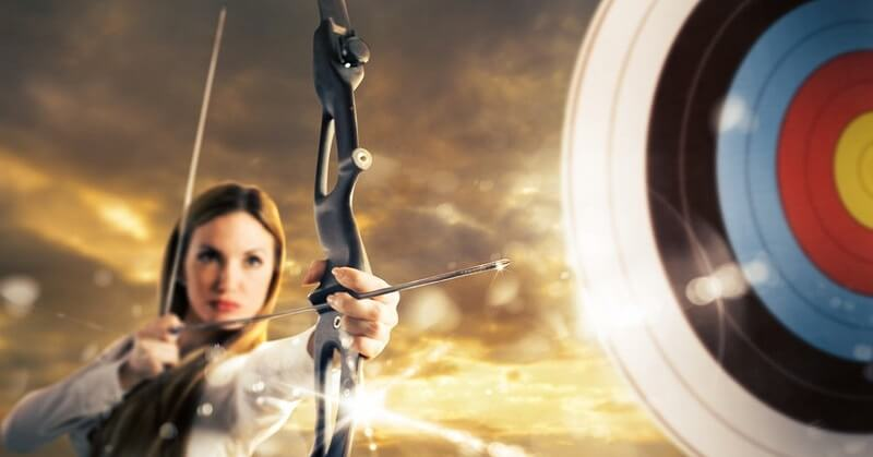 woman with bow and arrow aiming at target to signify setting goals