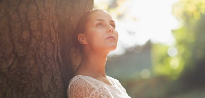 young woman sitting against tree pondering questions