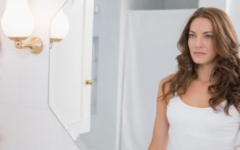 woman saying positive affirmations into bathroom mirror