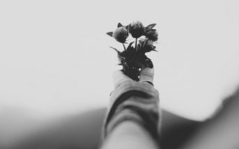 a person holding flowers to symbolize death