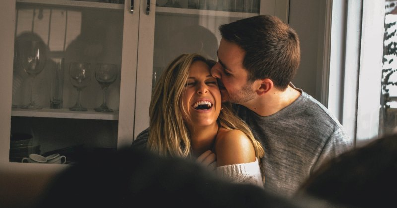 man and woman laughing and hugging