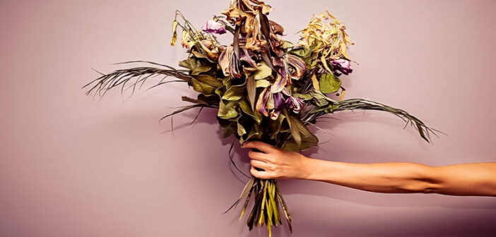 outstretched hand with bouquet of dying flowers