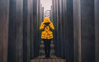 person in orange jacket walking down dark alley - running from problems
