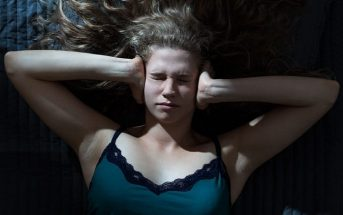 young woman lying down with hands over ears trying to stop her negative thoughts
