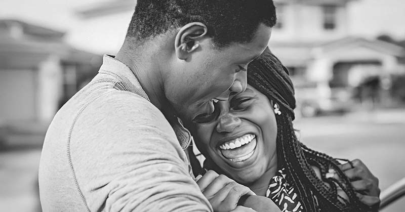 black and white photo of couple smiling and embracing - concept of falling back in love
