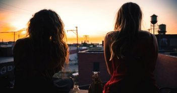 two friends talking while watching a sunset over a town