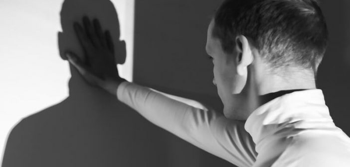 man holding hand up against his shadow on the wall illustrating the concept of self-sabotaging behavior