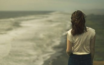 young woman looking out over ocean waves - concept of regret