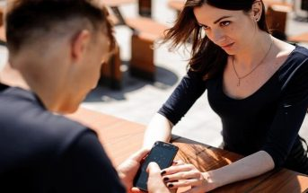 woman trying to get attention of boyfriend who's using his phone