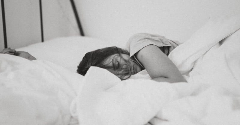 black and white photo of woman sleeping in bed