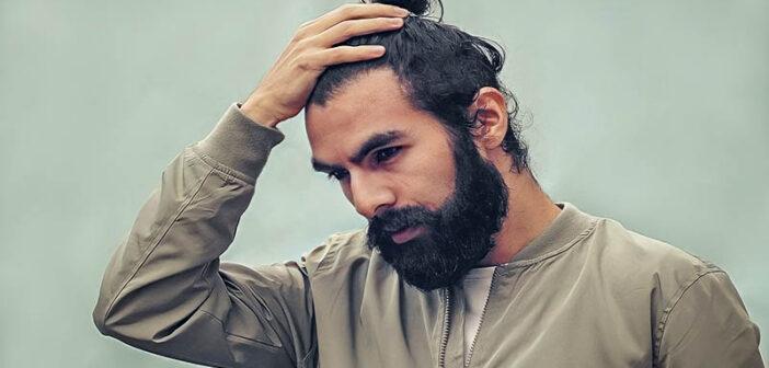 man with beard holding his head