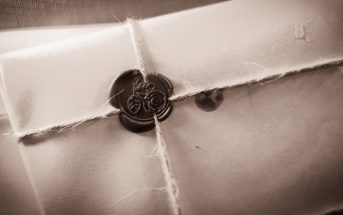 black and white photo of letter sealed in an envelope with string and wax