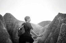 a woman walking through rock formations - concept of self-discovery