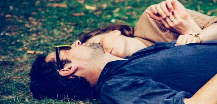 loved up couple in the honeymoon phase lying on grass