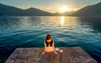 woman sitting on pier overlooking sunrise - concept of being patient