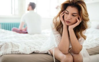 woman sitting on opposite side of bed to her partner indicating relationship difficulties