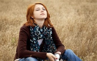 young woman sitting on grass, grounding herself