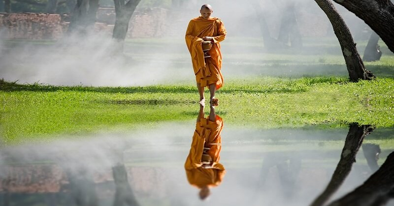 A Buddhist monk walking with reflection in water - concept of Nirvana