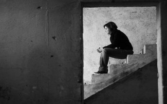 young woman sitting on steps facing adversity in life