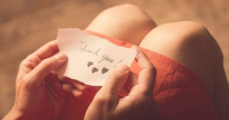 woman holding a thank you note