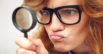 young woman looking through magnifying glass - illustrating being detail oriented
