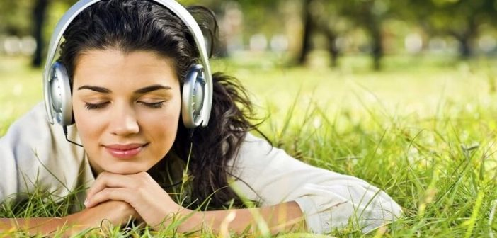 young woman lying on grass with headphones on illustrating music therapy