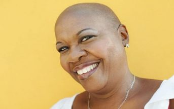 smiling black woman against yellow background - concept of a positive mental attitude