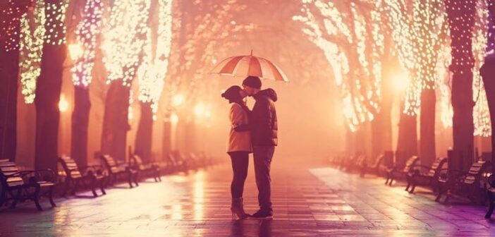 couple kissing under umbrella down a boulevard with lights