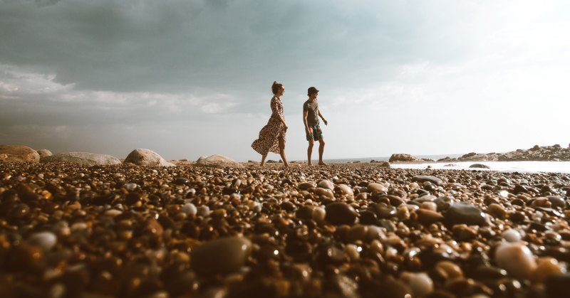 couple skipping stones at beach