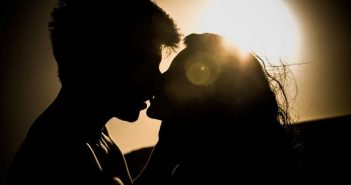 silhouette of young couple kissing against the sun - illustrating relationship myths